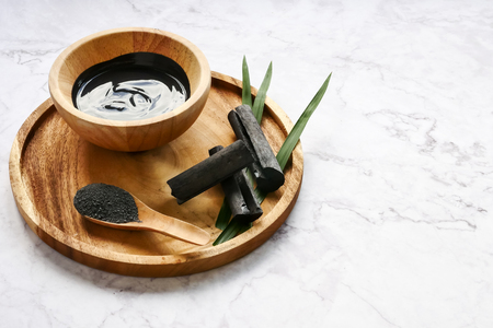 Facial mask and scrub by activated charcoal powder on marble table Banque d'images