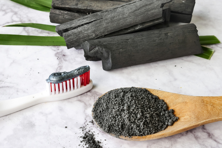 Toothpaste by activated charcoal powder on marble table Banco de Imagens - 104953749