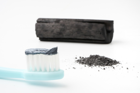 Toothpaste by activated charcoal powder on white background Stock Photo