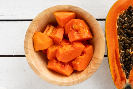 Slices of sweet papaya in wooden bowl on wooden table. 免版税图像