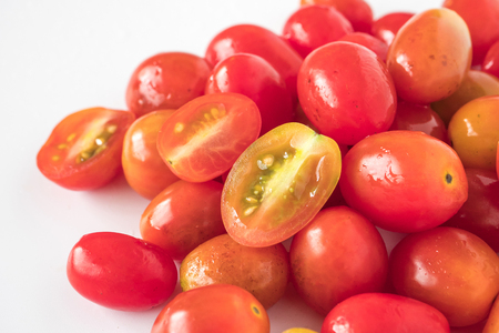 Close up of Fresh Plum tomatoes on white background.