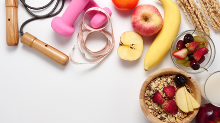 Top view of Oatmeal flakes, milk, fresh fruits and fitness equipments on white background. copy space Imagens