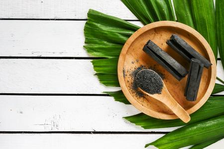 Bambusowy węgiel drzewny i proszek na drewnianym stole. skopiuj miejsce