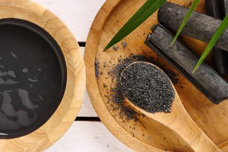 Masque facial et gommage par poudre de charbon actif sur table en bois Banque d'images