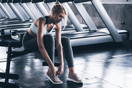 Young woman lacing sports shoes before exercise at the gym Stockfoto