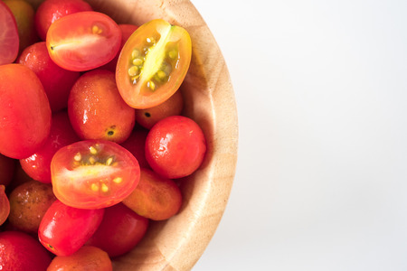 Close up of Plum tomatoes in wooden bowl on white background. copy space