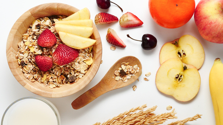 Top view of Oatmeal flakes, milk, and fresh fruits on white background. Imagens