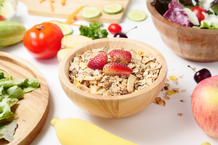 Close up of muesli, mixed vegetables salad and fresh fruits on white background.