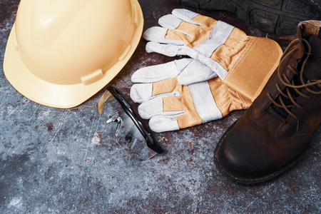 Sicherheit auf der Baustelle. Persönliche Schutzausrüstung auf rostigem altem Metallbeschaffenheitshintergrund Standard-Bild