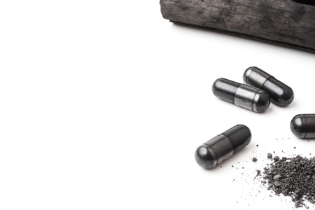 Charcoal (activated carbon) in capsules on white background. copy space