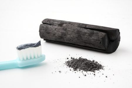 Toothpaste by activated charcoal powder on white background Banco de Imagens - 105487378