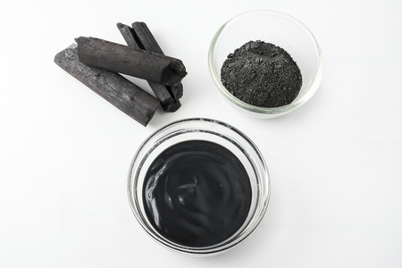 Facial mask and scrub by activated charcoal powder on white background Stock Photo