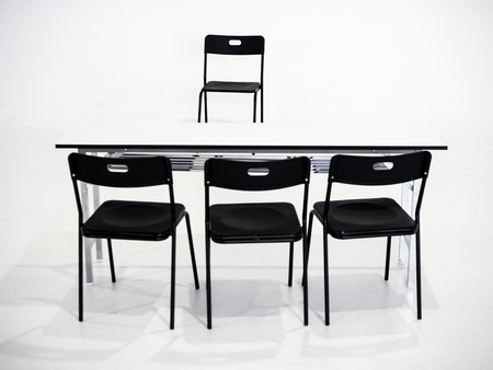 Black chairs with white table on white background. Interview place concept Stock fotó