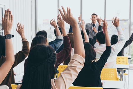 Audiencia levantando las manos mientras el empresario está hablando en formación en la oficina. Foto de archivo