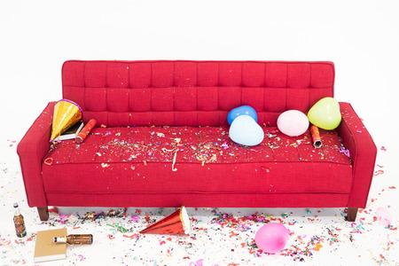 Caos en el sofá rojo después de la fiesta de año nuevo