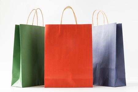 Bolsas de papel de colores sobre fondo blanco.