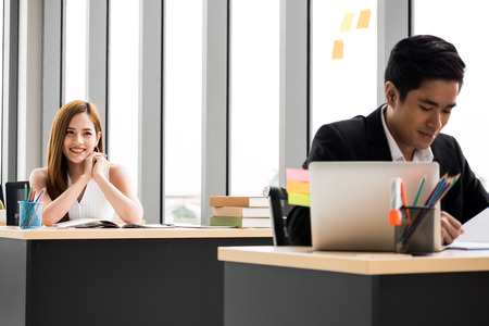 Beautiful Businesswoman is looking at Businessman at the office.