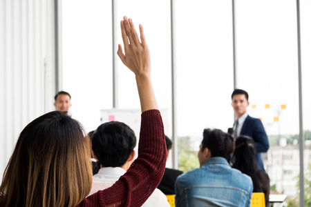 A woman is raising hand up while businessman is speaking in training at the office. Foto de archivo