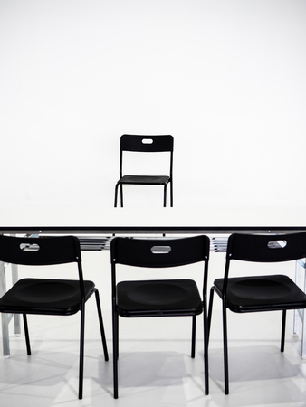 Black chairs with white table on white background. Interview place concept Stockfoto