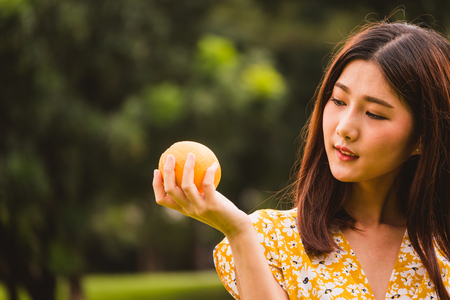 Beautiful woman holding orange standing in the park
