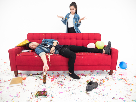 Young woman looking at drunk her boyfriend sleeping on sofa after new year party Stock Photo