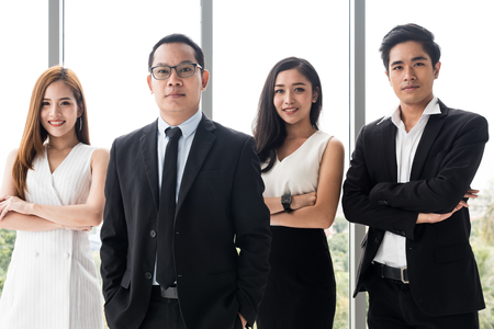 Asian Businesspeople are standing up and smiling at the office.