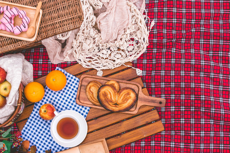 Summer picnic with a basket of food on blanket in the park. Free space for text