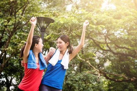 ヌーチュアの背景を持つスポーツウェアで2人の幸せな若い女の子