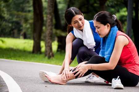 Asian woman is getting ankle injury while exercise in the park.