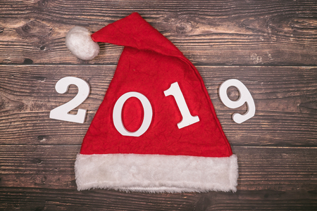 Top view of Christmas hat and 2019 number on wooden Stock Photo