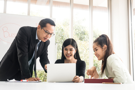Asian Businesspeople are brainstorming while meeting together at the office.