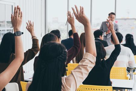 Publiek handen omhoog terwijl zakenman in opleiding op kantoor spreekt.