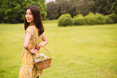 Beautiful woman in yellow dress holding a basket with flowers standing on grass in the park Stockfoto