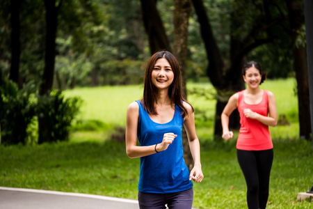 Portrait of young girl jogging in a park with her friend Stockfoto