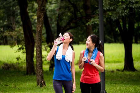 Attractive young women taking a break after exercise in a park
