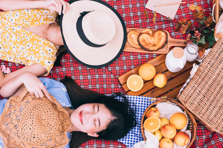 Two female friends enjoying picnic together in a park.