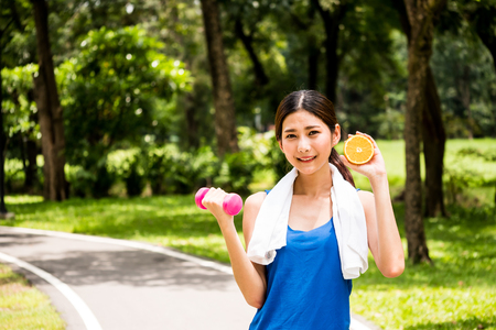 Portrait of attractive woman is holding dumbbell and orange in the park.