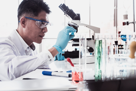 Scientist doing some research and looking through a microscope in a laboratory