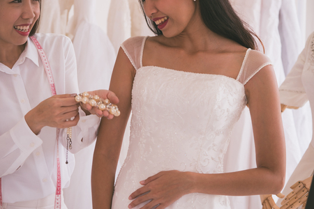 Bride fitting dress in atelier with wedding assistant.