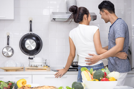Couple preparing food for dinner in kitchen at home