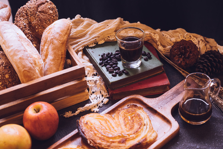 Baked breads, apples and coffee on a table.