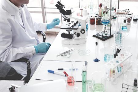 Wissenschaftler, der in einem Labor forscht und durch ein Mikroskop schaut Standard-Bild