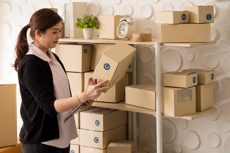Business woman online seller checking parcel boxes prepare for delivery to customers Stockfoto
