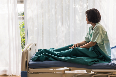 Lonely elderly female patient sitting on bed at hospital and looking away outside the window waiting to see her family to visit.