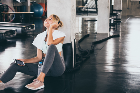 Young happy woman sitting and listening to music by smartphone while having exercise break at the gym.