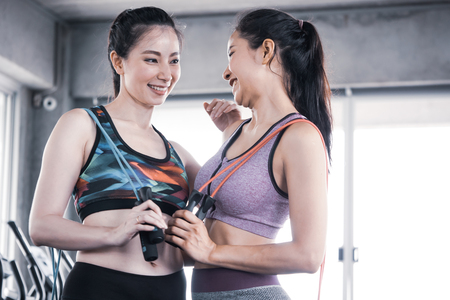 Attractive young women in sportswear with skipping rope at the gym
