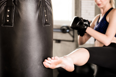 Sportswoman kicking punching bag during boxing practice in fitness gym