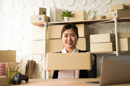 Happy woman success in her owner small business online with package box.