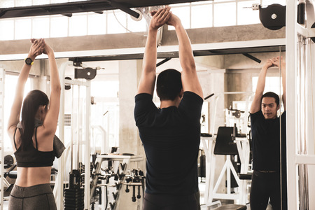 Young couple stretching and warming up before workout at the gym