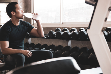 Attractive young man taking a break after exercise at the gym